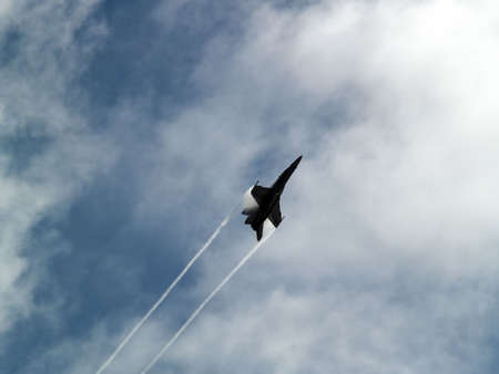 f18: F-18 Hornet climbing rapidly with supersonic contrail Stock Photo