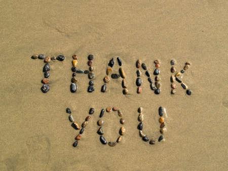 Thank you phrase written on beach sand photo