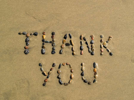 Thank you phrase written on beach sand Stock Photo