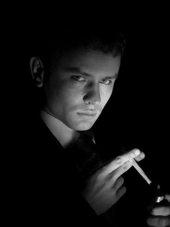 Young man in suit smoking cigarette looking into camera photo