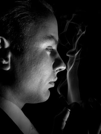 Young man in suit smoking cigarette sideview Stock Photo