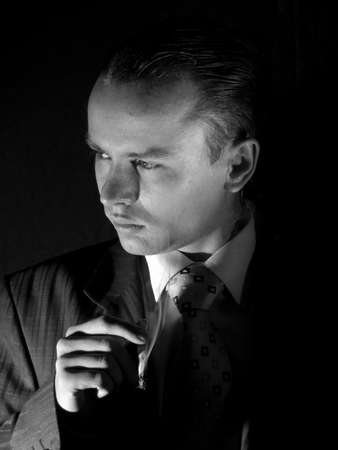 Young man in suit smoking cigarette side-view photo