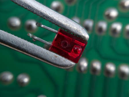 Red LED in pincers elctronic assembly macro Stock Photo