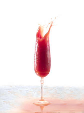 Tomato juice splash in glass white background photo