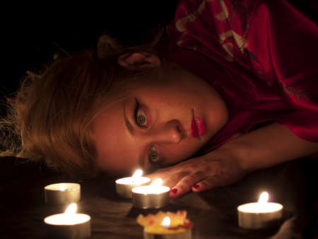 Beautiful blonde lady with oriental make-up lying in candles Stock Photo - 4295889