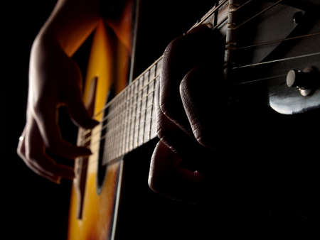 women's hand: Female hands playing acoustic guitar on black background