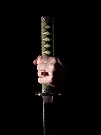 jewel hands: Japanese katana sword in mans hand in darkness