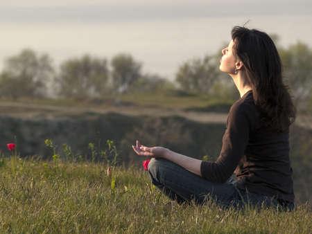 Mujer joven meditando en la cima de la colina de al aire libre Foto de archivo - 4781700