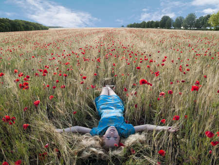 Beautiful blonde lady laying in poppy field Stock Photo
