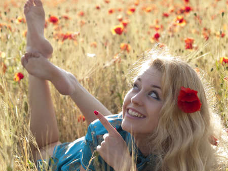 Beautiful Barefoot blonde lady laying in poppy field Stock Photo - 5089304