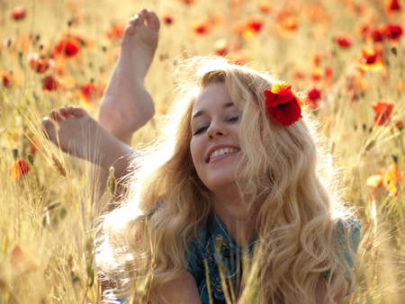 poppy field: Barefoot mooie blonde dame tot in papaverbolkaf veld Stockfoto