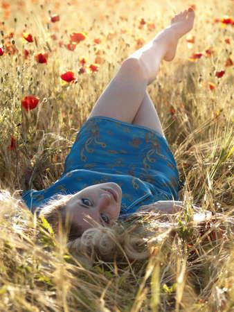Beautiful Barefoot blonde lady laying in poppy field photo