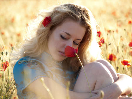 Beautiful blonde lady sitting in poppy field and smelling popy