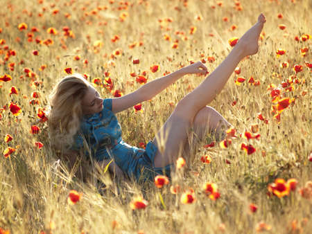 Beautiful Barefoot blonde lady laying in poppy field photo