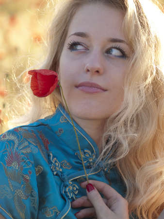 Beautiful blonde lady with poppy flower outdoors