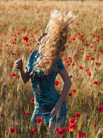Beautiful blonde lady in poppy field shaking hair photo