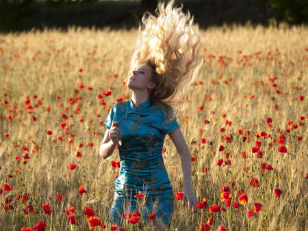 Beautiful blonde lady in poppy field shaking hair