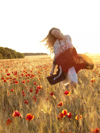 Beautiful blonde lady walking in poppy field on sunset photo