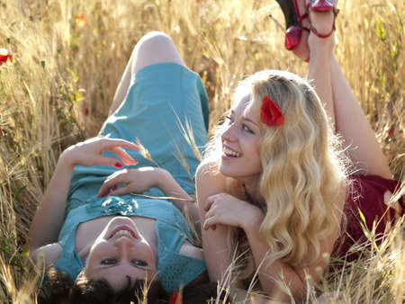 Two beautiful young ladies laying in wheat field photo