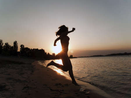 Lady in bikini jumping into water on sunset photo