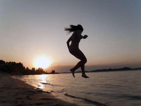 Lady in bikini jumping into water on sunset photo