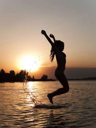Lady in bikini jumping above water on sunset photo