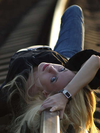 Young blond woman in casual dress lying on rail photo