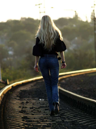 Young blond woman in casual dress walking by railway
