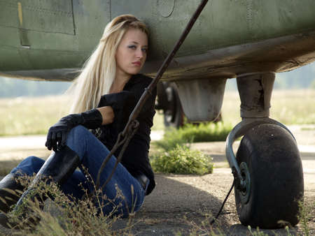 Young blond woman sitting on ground near vintage airplane Stock Photo - 5566887