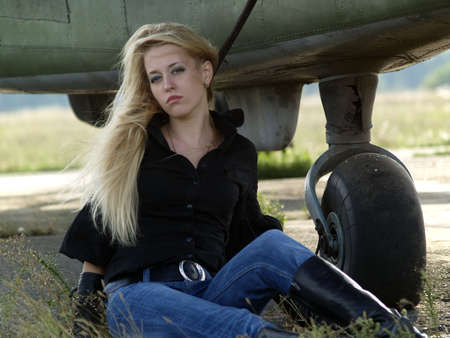 Young blond woman sitting on ground near vintage airplane photo
