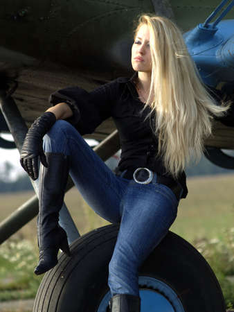 Young blond woman sitting on vintage airplane landing gear Stock Photo