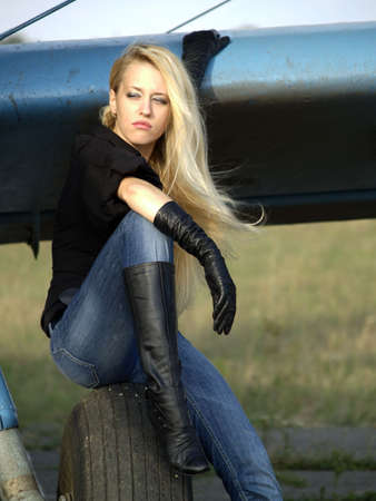 Young blond woman sitting on vintage airplane landing gear Stock Photo - 5566889