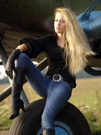 assis par terre: Youg femme blonde assise sur les engins de d�barquement vintage avion