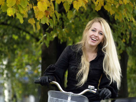 Young beautiful blond woman on bicycle under maple tree. Fall Stock Photo