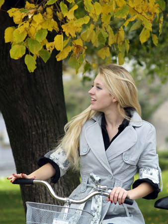 Young beautiful blond woman on bicycle under maple tree. Fall photo