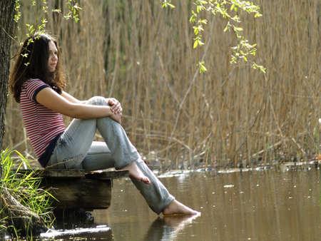 Girl in straw hat sitting near lake shore photo