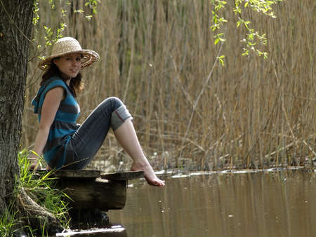 Girl in straw hat sitting near lake shore photo