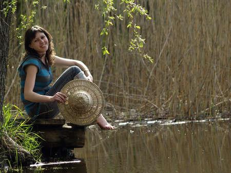 Chica en el sombrero de paja sentado cerca de orilla del lago photo