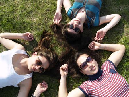 Tres muchachas jóvenes imposición sonriente de hierba photo