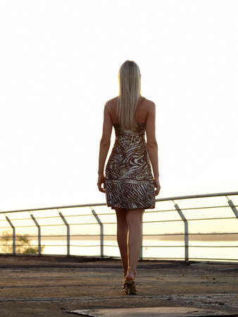Beautiful blond woman in leopard dress walking over promenade