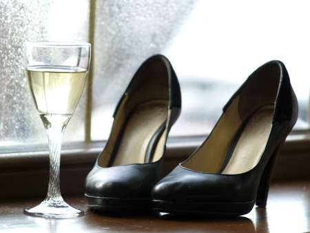 Pair of female shoes on heels and a glass of wine on window Stock Photo