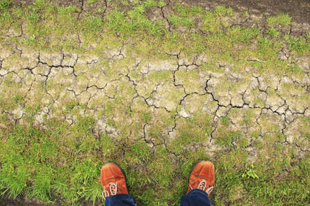 patchy: Orange boots on patchy ground from above Stock Photo