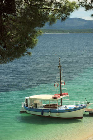 brac: Boat anchored near sandy beach in Mediterranean sea