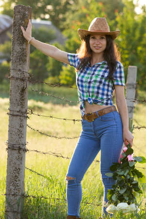 Young white girl in country style dress with flowers leaning on fence Stok Fotoğraf
