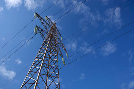 brassy: There is a power transmission line by an interesting angle of view under blue sky. Stock Photo