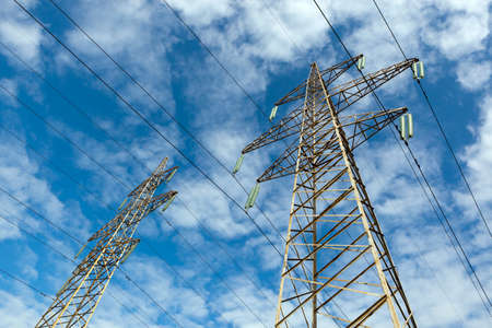 brassy: There is a power transmission line by an interesting angle of view under blue sky with clouds.