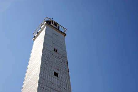 青い空の下で古い木造灯台。 写真素材
