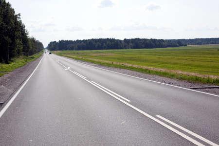 白い雲と青い空の下の高速道路があります。 写真素材