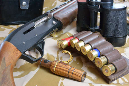 ammo: some large-caliber ammoes in the ammo bag, binoculars, gun and duck call Stock Photo