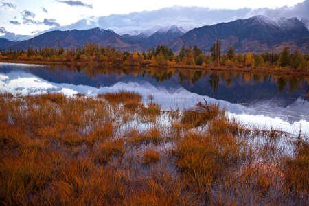 Autumn mountain landscape with still water river